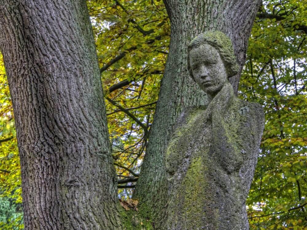 Steinfigur vor Baumstamm, Foto: Adobe Stock, k_rahn